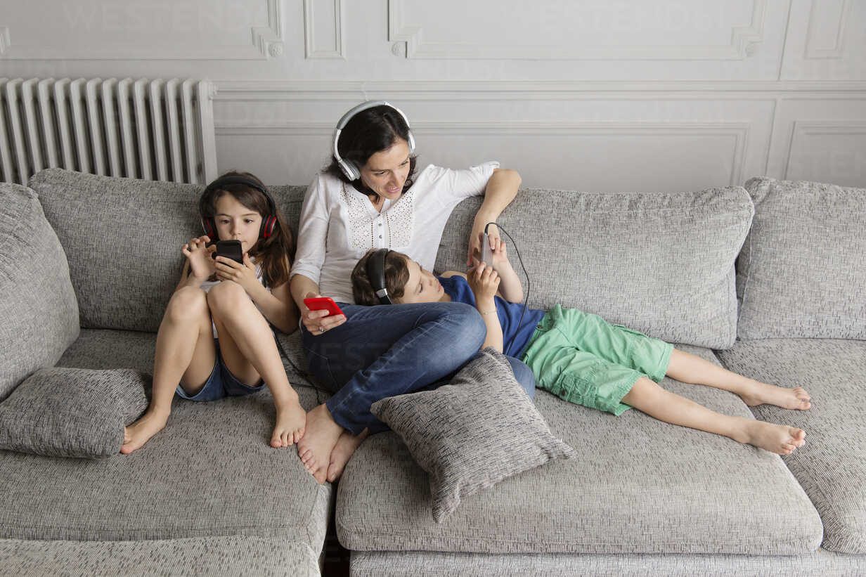 Mother and her children sitting on the couch listening music with their headphones and smartphones - LITF000285 - Lisa Tichane/Westend61