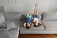 Two little children playing on the couch upside down with their legs in the air - LITF000288