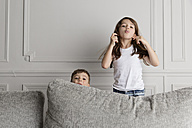 Two little children pulling funny faces behind the couch - LITF000291