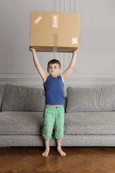 Portrait of little boy holding a cardboard box over his head at home - LITF000294