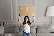 Portrait of little boy holding a cardboard box on top of her head at home - LITF000300