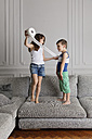 Girl wrapping toilet paper around her little brother at home - LITF000303