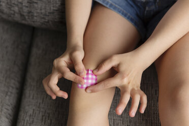 Little girl's hands putting a band-aid on her knee, close-up - LITF000306