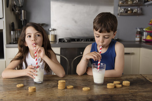 Little boy and girl sitting at kitchen table blowing bubbles in a glass of milk - LITF000309