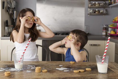 Little girl and boy covering their eyes with cookies - LITF000312