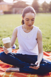 Student at the park having a coffee to go, looking on smartphone - GIOF000955
