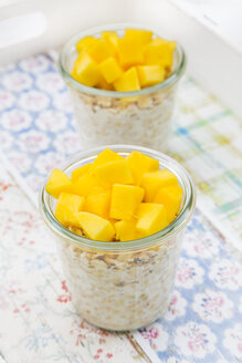 Two glasses of overnight oats with diced mango on tray - LVF004854