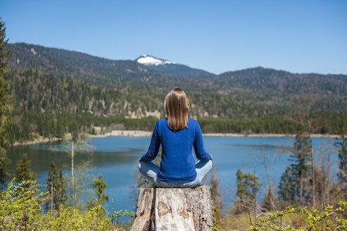 Germany, Bavaria, woman relaxing at lake Barmsee - DIGF000470