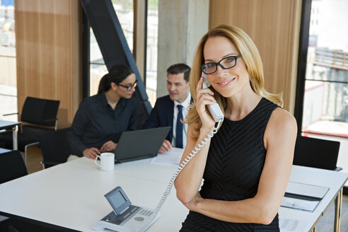Portrait of smiling businesswoman on the phone with colleagues in background - CHAF001702