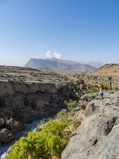 Oman, Jebel Shams, woman standing on viewing point - AMF004882