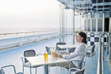 Young man having a beer on deck of cruise ship - SEF000902