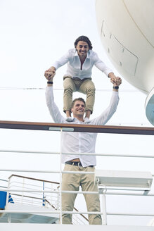 Two young men messing about on cruise ship, balancing on shoulders - SEF000908
