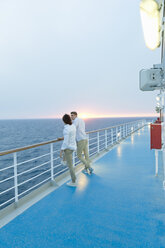 Young men standing on deck of ship, watching sunset - SEF000911