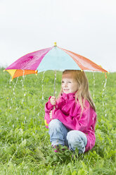 Young girl crouching with umbrella on meadow, rainy weather - MAEF011614