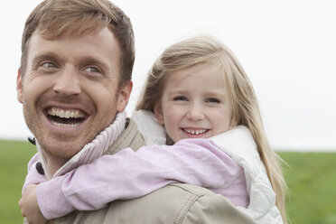Happy father carrying daughter piggyback outdoors - MAEF011622