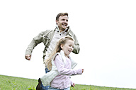 Happy father and daughter running in meadow - MAEF011628