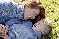 Carefree mother and son lying in meadow - MAEF011634