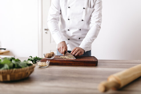 Chef preparing stuffing for ravioli, chopping nuts - JRFF000636