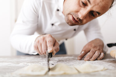 Chef cutting fresh ravioli - JRFF000657