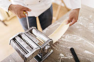 Chef rolling dough with pasta machine - JRFF000660