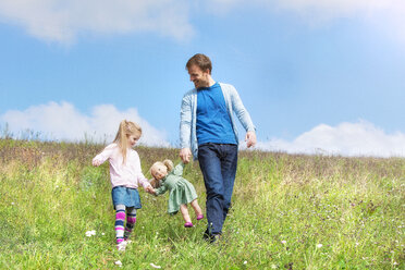 Happy father and daughter walking with doll in meadow - MAEF011646