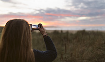 Back view of teenage girl taking photo of sunset with her smartphone - MGOF001818