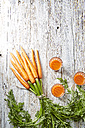 Bunch of carrots and three glasses of carrot juice on wood - KSWF001764