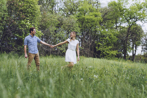 Couple in love holding hands while walking on a meadow - GIOF000985