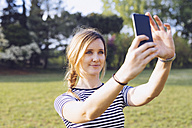 Portrait of relaxed blond woman taking selfie with smartphone - GIOF001000