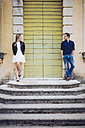 Italy, Verona, couple standing besides wooden door looking at each other - GIOF001006