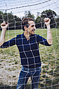 Laughing man standing behind football net - GIOF001009