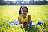 Portrait of young woman with smartphone relaxing on a meadow - GIOF001027