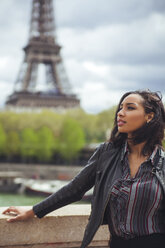 France, Paris, Young woman standing on bridge with theEiffel Tower in background - ZEDF000114