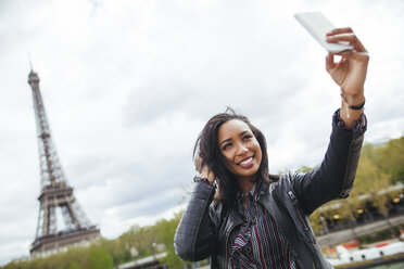 France, Paris, Young woman taking smart phone selfie in front of Eiffel Tower - ZEDF000117