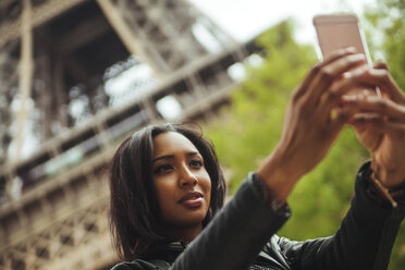 France, Paris, Young woman taking smart phone selfie in front of Eiffel Tower - ZEDF000120