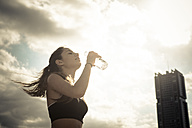 Athletic teenage girl drinking water from bottle - SIPF000451