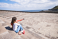 Two friends sitting on stairs at the coast taking a selfie - SIPF000457