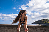 Athletic teenage girl standing at the ocean - SIPF000466