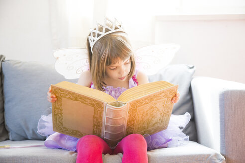 Portrait of little girl dressed up as fairy queen reading book - LVF004877