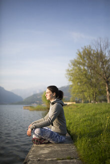 Italy, Lecco, relaxed young woman sitting at the lakeshore - MRAF000041