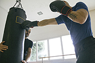 Boxer hitting a punching bag held by a training partner - ABZF000483