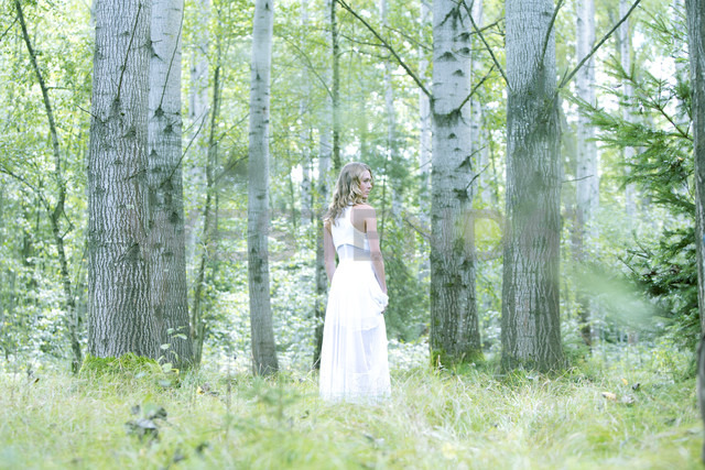 Young woman wearing white dress in the forest - MAE011711