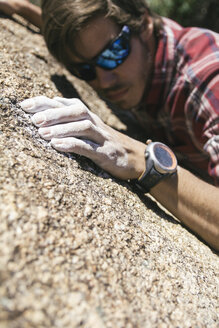 Hand of a climber with sunglasses with powder chalk magnesium during a climbing - ABZF000520
