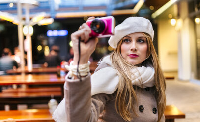 Portrait of young woman wearing beret taking selfie with digital camera - MGOF001822