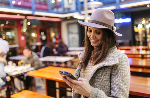 Portrait of smiling young woman looking at her smartphone - MGOF001828