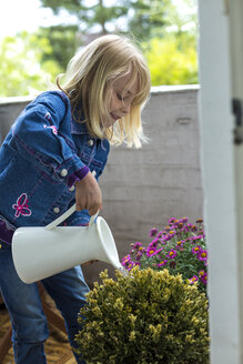 Blond little girl watering plants on balcony - JFEF000794