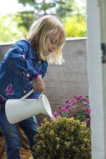 Blond little girl watering plants on balcony - JFEF000794