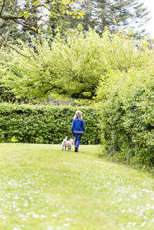Back view of little girl walking with her dog in nature - JFEF000797