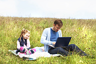 Father and daughter sitting on meadow, smartphone and laptop - MAEF011727