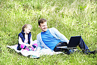 Father and daughter sitting on meadow, father working on laptop - MAEF011730